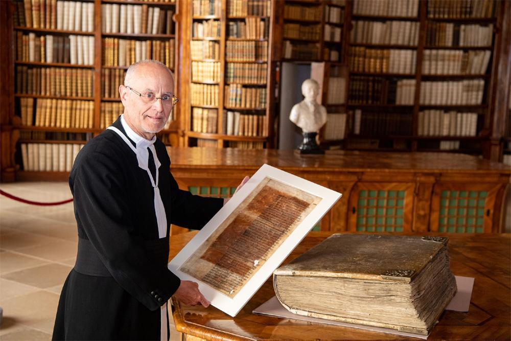 Chorherr mit Riesenbibel in der Bibliothek des Stiftes St. Florian - Foto: Kerschbaummayr
